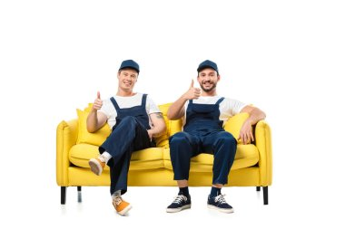 two movers in uniform sitting on yellow sofa, showing thumb up signs and looking at camera isolated on white