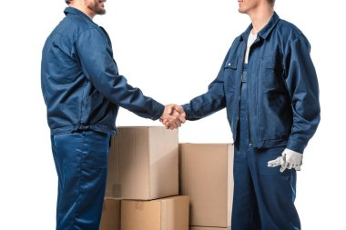 cropped view of two movers in uniform shaking hands near cardboard boxes isolated on white