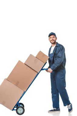 Smiling handsome mover in uniform transporting cardboard boxes on hand truck isolated on white stock vector