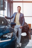 selective focus of cherful man in glasses standing near automobile with crossed legs in car showroom