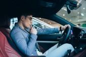 Fotografia pensoso uomo elegante in occhiali pensando tenendo volante in automobile