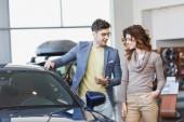 šťastný muž v brýlích ukazováčku v automobilu blízko kudrnaté ženy s rukou v kapse