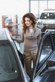 cheerful curly woman standing near vehicle in car showroom