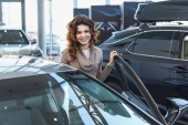 happy curly woman smiling while standing near vehicle in car showroom
