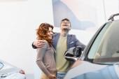 selective focus of happy man hugging curly woman in car showroom