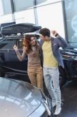 fröhlicher Mann mit Brille umarmt lockige attraktive Frau, während er Triumph im Autohaus feiert
