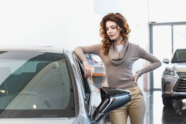 beautiful curly woman standing near vehicle in car showroom