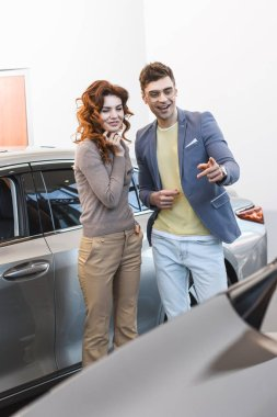 cheerful curly woman standing with happy man pointing with finger at car