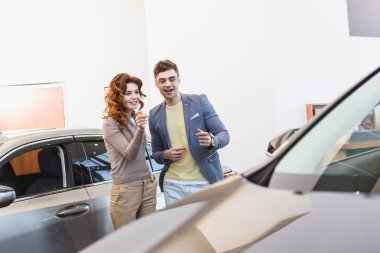 selective focus of cheerful curly woman and happy man pointing with fingers at car
