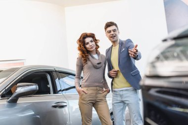 selective focus of curly woman standing with hand in pocket near man pointing with finger at car