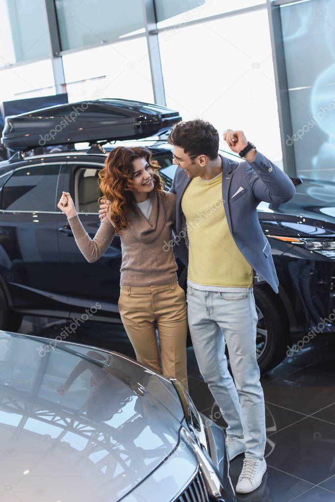 uomo allegro in occhiali abbracciare ricci donna attraente mentre celebra trionfo in auto showroom