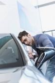 selektivní zaměření úspěšného stylového muže v brýlích, které stojí nedaleko auto v autosalónu