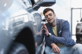 selektivní zaměření štastného stylového muže v brýlích s úsměvem u auto v autosalónu