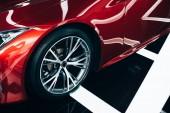 zářivý nový červený automobil s kovovým kolečkem v autosalónu