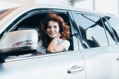 selective focus of cheerful curly woman smiling while sitting in automobile