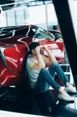 rozrušený muž sedící u červeného automobilu v autosalónu