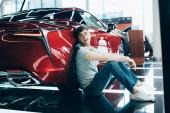 Fotografie pohledný muž sedící u červeného auta v autosalónu