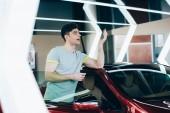 Fotografie selektivní zaměření šťastného muže, který drží klíče od auta, když stojí u nového auta