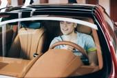 Fotografie selektivní zaměření pohledného šťastného muže sedícího u volantu v novém autě
