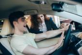 selektivní zaměření vzrušeného muže sedícího v novém autě v blízkosti automobilového dealera