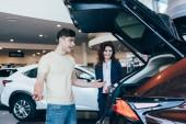 selektivní zaměření obchodníka s autem a šťastného zákazníka stojícího v blízkosti nového auta