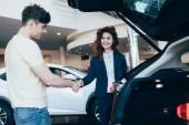 Fotografie Gut gelaunter Autohändler und Kunde beim Händeschütteln im Autohaus