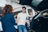 Fotografie Selektiver Fokus glücklicher Mann und Autohändler beim Händeschütteln im Autohaus