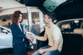 selective focus of happy man and pretty car dealer shaking hands in car showroom