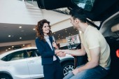 cheerful car dealer and customer shaking hands while standing near new car