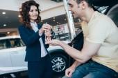 Fotografie Selektiver Fokus des lächelnden Autohändlers, der dem glücklichen Kunden Autoschlüssel gibt