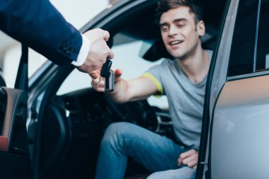 cropped view of car dealer giving keys to successful man sitting in car