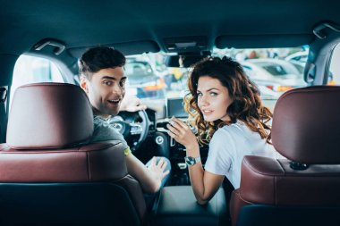 selective focus of happy man and curly cheerful woman looking at camera while sitting in automobile