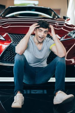 handsome excited man sitting near new red luxurious car