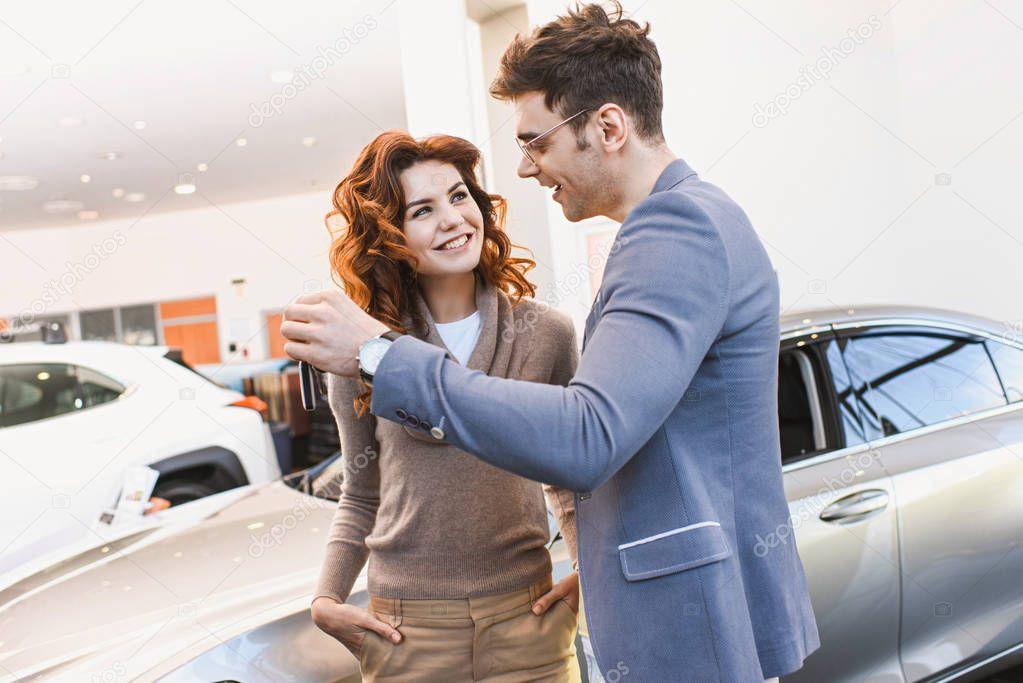 felice uomo in occhiali guardando allegra donna riccia in piedi con le mani in tasca in auto showroom
