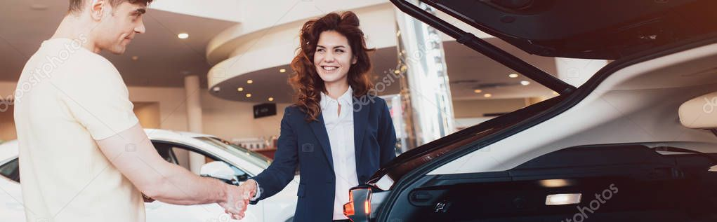colpo panoramico di concessionario auto sorridente e cliente che stringe la mano nello showroom auto
