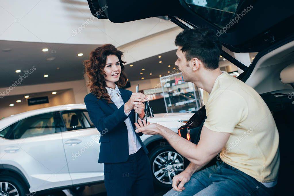 fuoco selettivo del cliente felice che prende le chiavi dell'automobile dal commerciante attraente dell'automobile