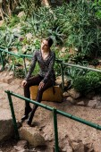 Fotografie Dreamy sexy woman in black pantyhose sitting on suitcase in botanical garden