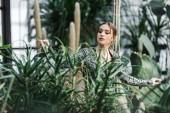 Attraktive nachdenkliche junge Frau, die Bewässerung von grünen Pflanzen in der Orangerie