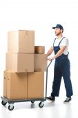 Fotografie handsome mover in uniform transporting cardboard boxes on hand truck isolated on white