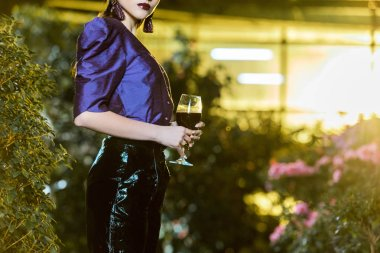 Xropped view of stunning young woman in purple blouse holding wine glass in orangery