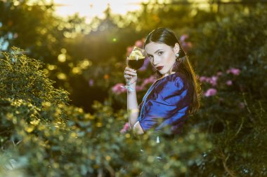 Stunning young woman in purple blouse holding wine glass in botanical garden