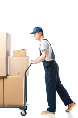 mover in uniform transporting cardboard boxes on hand truck isolated on white