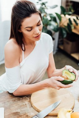 High angle view of pretty stylish girl holding cut avocado near table in kitchen stock vector