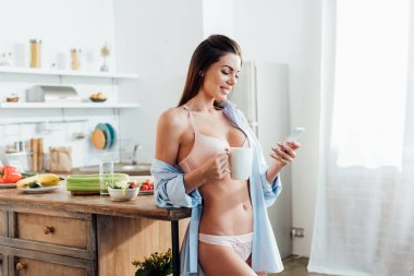 Cheerful girl in white lingerie holding cup of coffee and using smartphone