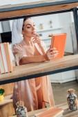Kíváncsi nő a housecoat törülközővel a fej Holding könyv