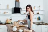 Zúčastněná žena ve spodním prádle a zástěře stojící blízko dřevěného stolu v kuchyni