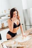Sexy žena v černém prádle, při hnětení těsta v kuchyni