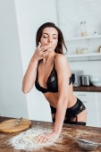 Sexy woman in black lingerie licking finger while kneading dough in kitchen