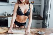Levágott kilátás szexi nő fekete fehérnemű gördülő ki tésztát hengercsapos