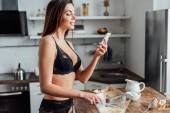 Woman in black lingerie whipping eggs with whisk and holding smartphone in kitchen